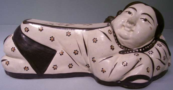 Pillow in the form of a reclining girl, Northern China, Jin dynasty (1115-1234), Cizhou ware, high-fired ceramic with overglazed decoration, The Avery Brundage Collection, B60P422. The representation of girls on a Song pillow, rare in contrast to the frequent representations of boys, suggests a piece made for female use. This finely sculpted pillow features a young girl, her expression well detailed, accompanied by chrysanthemum and plum blossoms.